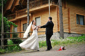 Wedding couple dancing on the background of a wooden house — Stock Photo