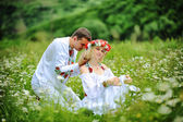 Young  beautiful couple in traditional dress at the field of whi — Stock Photo
