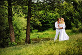 Young  beautiful couple in traditional dress under the tree — Stock Photo