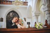 Young beautiful wedding couple at the old catholic church — Stock Photo