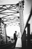 Young beautiful wedding couple at the train bridge — Stock Photo