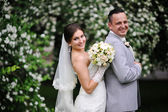 Wedding couple in love near white flowers trees — Stock Photo