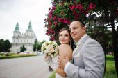 Happy married hugging on background church — Stock Photo