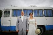 Funny newlyweds stay on background old bus — Stock Photo