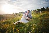 Newlyweds on sunset with flowers — Stock Photo