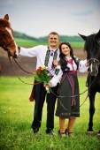 Young couple on national dress with horses — Stock Photo