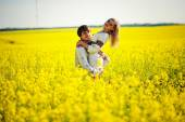 Couple on traditional dress at yellow flowers field — Stock Photo