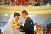Bride and groom dancing in the restaurant on bubbles — Stock Photo