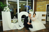 Wedding couple siting on background decor words LOVE — Stock Photo