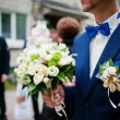 Groom  at blue jacket and bow tie with bouquet — Stock Photo #78234834
