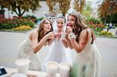 Young bridesmaid with bride drinking coffee — Stock Photo