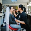 Постер, плакат: Make up artist doing make up for young beautiful brunette bride