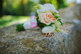 Wedding bouquet with rings on stone — Stock Photo