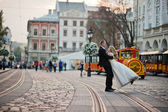 Groom hold on hand bride background city with kids train — Stock Photo