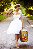 Beautiful redhead bride with suitcases — Stock Photo
