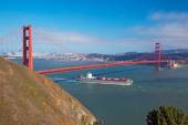 Golden Gate & cargo ship passing below — Stok fotoğraf