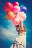 Happy girl playing with balloons - retro and vintage style — Stock Photo