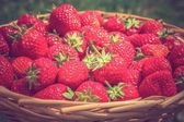 Fresh red strawberries in wooden knitting basket — Stock Photo