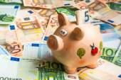 Piggy bank in a pile of euro money — Stock Photo