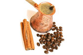 Coffee in vintage copper turkish coffee pot (cezve) , coffee beans and cinnamon sticks on white — Stock Photo