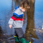 Cute little boy running through puddles — Stock Photo #70957467