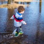 Cute little boy running through puddles — Stock Photo #70957473