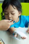 Illness asian kids writing paper on desk and eating cereal, sali — Stock Photo