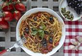 Italian food, pasta with tomatoes, olives and capers, called put — Stock Photo