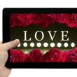 Tablet PC in hand with frame with love card with bush of red rose flowers and play of light on defocusing blur led lamps background on screen isolated on white — Stock Photo #78408192