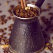 Turkish coffee pot filled with coffee beans and cinnamon stick on canvas background with spices scattered on it, vintage filtered — Stock Photo #70936609