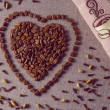 Coffee beans in a shape of a heart on canvas background with spices scattered on it, towel,  vintage filtered — Stock Photo #70936629