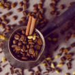 Turkish coffee pot filled with coffee beans and cinnamon stick on canvas background with spices scattered on it, vintage filtered — Stock Photo #70936635