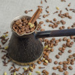 Turkish coffee pot filled with coffee beans and cinnamon stick on canvas background with spices scattered on it — Stock Photo #70936639