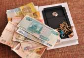 Ruble, hryvnia, jewelry and mini-safe on a homogeneous backgroun — Stock Photo