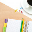 Coffee mug, pencils, and a pad on a wooden table — Stock Photo #70903989