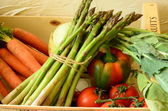 Peppers, asparagus, carrots and tomatoes in wooden box — Stock Photo