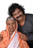Adult son and his ageing mother. India Senior Woman with her son on white — Stock Photo
