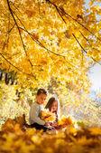 Pensive kids sittin on a log in the autumn park — Stock Photo