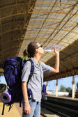Backpackers girl waiting for the train, girl drinks water — Stock Photo