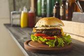 Hamburger on wooden table — Stock Photo