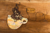 Coffee cup of colored paper full of coffee beans placed on wooden table — 图库照片