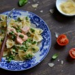 Pasta with salmon and green peas in a creamy sauce in a vintage plate on a dark surface — Stock Photo #73176205