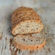 Homemade whole wheat bread with flax seeds on wooden surface — Stock Photo #73177323