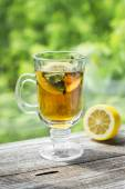 Green tea with mint and lemon in a glass mug — Stock Photo