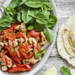 Stir fry of chicken breast and sweet red peppers, fresh spinach and homemade tortillas — Stock Photo #76735331