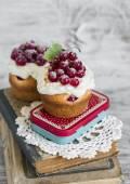 Кексы с сливками и красная смородина на светлом фоне деревянные — Стоковое фото