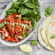 Stir fry with chicken breast, red peppers and onions, fresh spinach and homemade tortilla — Stock Photo #79047764