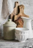 Vintage crockery and kitchen utensils - ceramic bowls, enamelled jug and container, cutting boards olive — Stock Photo