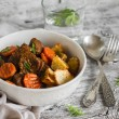 Beef stew in tomato sauce and roasted potatoes in a white bowl — Stock Photo #82081624