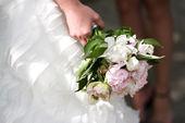 Gentle wedding bouquet with peonies in hands of the bride — Stock Photo